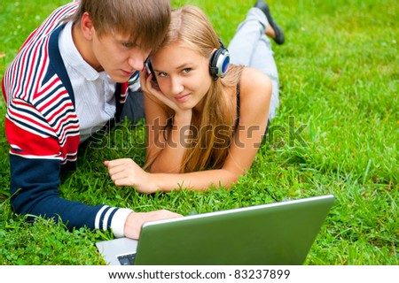 Happy young couple using laptop while lying on grass - stock photo