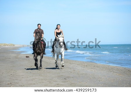 happy young couple vacation riding horses on the beach in sunny summer day - stock photo