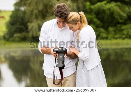 happy young couple viewing pictures on camera outdoors - stock photo