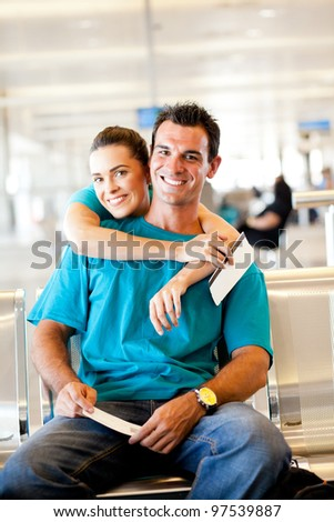 happy young couple waiting for their flight at airport - stock photo