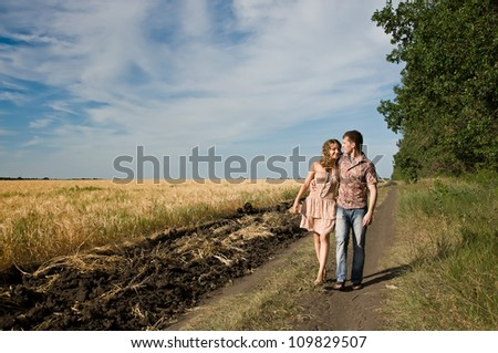 Happy young couple walking on a field - outdoors - stock photo