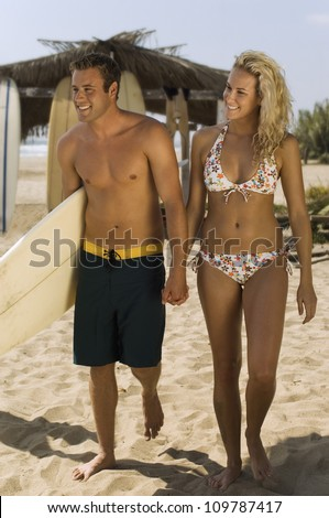 Happy young couple walking on beach holding hands - stock photo