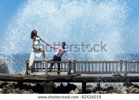 Happy young couple walking on the old pier. Ocean waves beating on the rocks - stock photo
