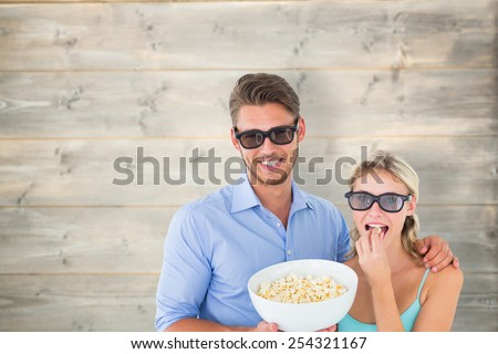 Happy young couple wearing 3d glasses eating popcorn against bleached wooden planks background - stock photo