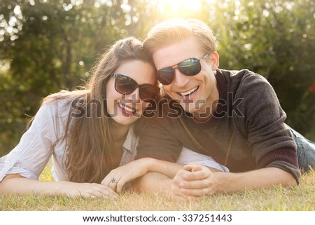 Happy young couple wearing sunglasses lying in the grass - stock photo