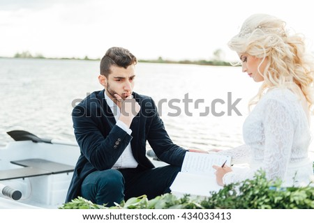 Happy young couple with a bouquet and a wreath hug sitting in a boat on the lake and sky background, lifestyle, love, relationships - stock photo