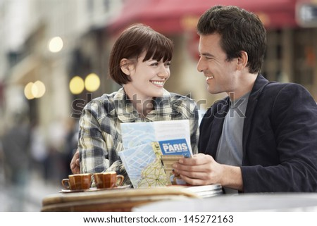 Happy young couple with a guidebook at an outdoor cafe - stock photo