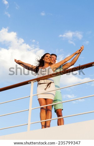 happy young couple with arms outstretched on cruise ship - stock photo