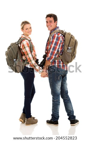 happy young couple with backpacks looking back on white background - stock photo