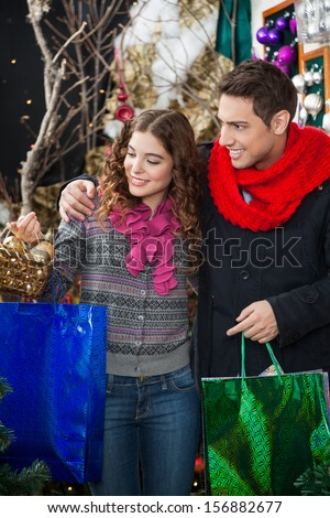 Happy young couple with bags and bauble basket shopping in Christmas store - stock photo