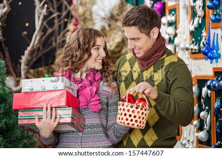 Happy young couple with Christmas presents and bauble basket in store - stock photo