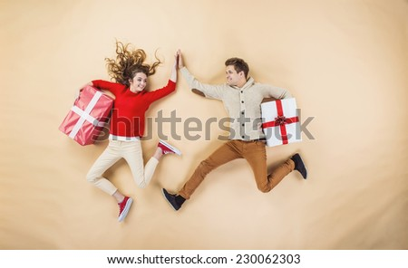 Happy young couple with Christmas presents jumping against the beige background - stock photo