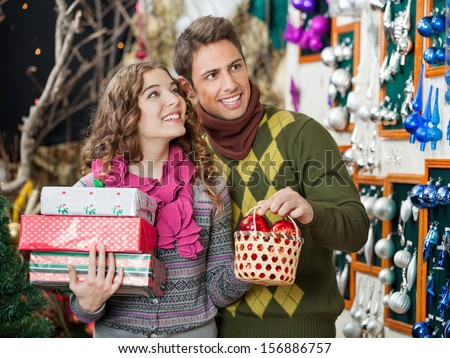 Happy young couple with Christmas presents shopping in store - stock photo