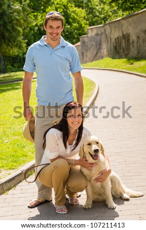 Happy  young couple with dog posing on sunny park alley - stock photo