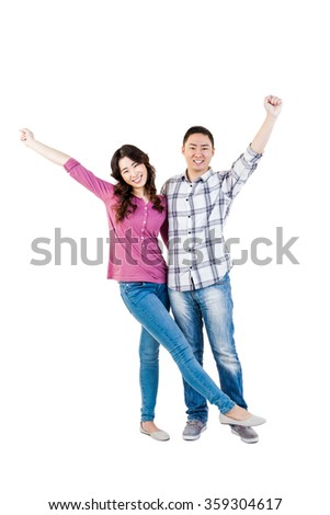 Happy young couple with hands raised standing over white background - stock photo