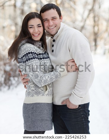 Happy young couple with mistletoe having fun in the winter park - stock photo