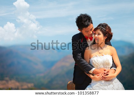 Happy young couple with mountain backgrond - stock photo