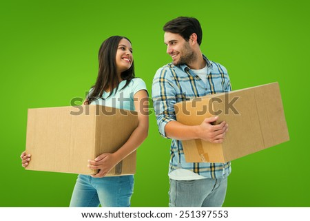 Happy young couple with moving boxes against green vignette - stock photo