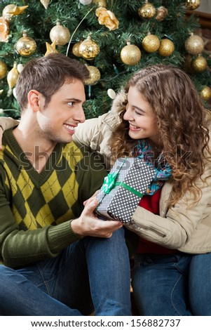 Happy young couple with present sitting against Christmas tree in store - stock photo