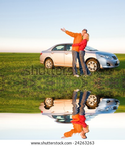 Happy young couple with their new car - stock photo