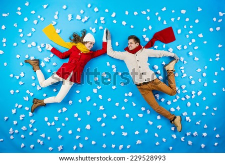 Happy young couplein winter clothes having fun against the blue background with snowflakes - stock photo