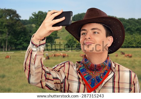 Happy young cowboy making selfie photo with smart phone. He is wearing brown cowboy hat, plaid shirt and colored bandana neckerchief - stock photo