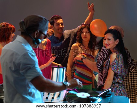 happy, young crowd dancing to the dj's music in a night club - stock photo