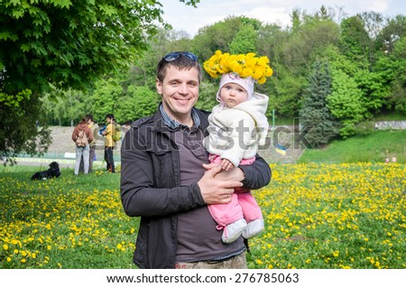 Happy young dad holding his baby little girl with a bouquet of flowers of dandelions on his head and smiling Family - stock photo
