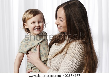 Happy young daughter with mother, smiling - stock photo
