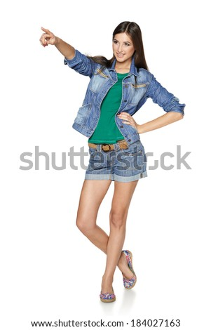 Happy young denim girl in shorts and jacket standing casually in full length, pointing to the side at blank copy space, against white background - stock photo
