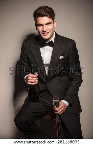 Happy young elegant business man sitting on a chair while enjoying a glass of champagne. - stock photo