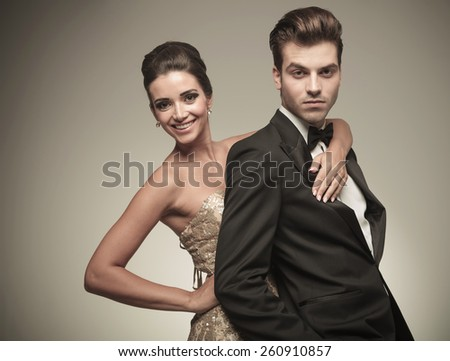 Happy young elegant woman embracing her husband from the back. Both looking at the camera. - stock photo