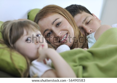 happy young family at home relaxing in bed - stock photo