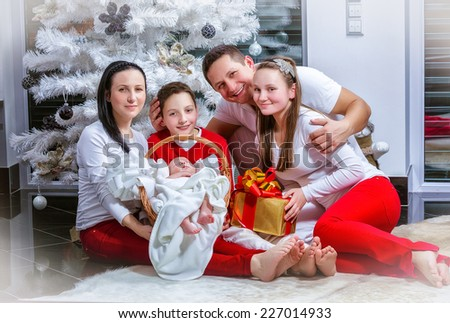 Happy young family at the Christmas tree - stock photo