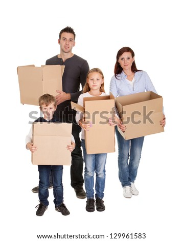 Happy young family carrying cardboard boxes. Isolated on white - stock photo