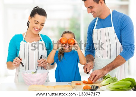 happy young family cooking in kitchen at home - stock photo