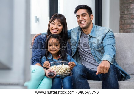 Happy young family eating popcorn while watching tv in living room - stock photo