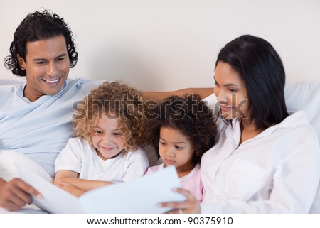 Happy young family enjoys reading a story together - stock photo