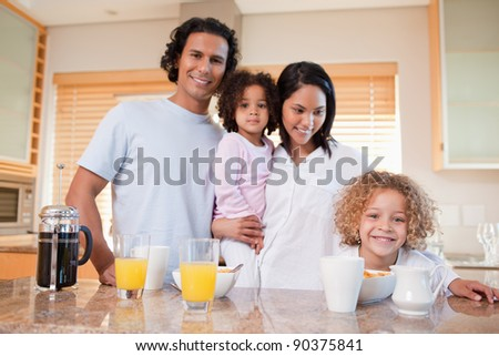 Happy young family having breakfast in the kitchen together - stock photo