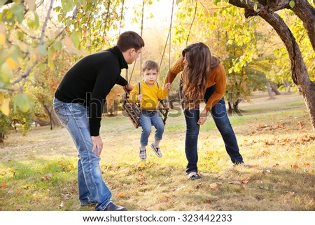 Happy young family having fun on a swing ride at a garden a autumn day - stock photo