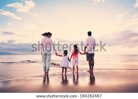 Happy Young Family Having Fun on Beach at Sunset - stock photo