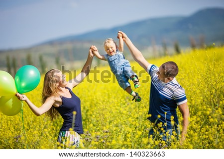 Happy young family having fun outdoors on a summer day  - stock photo