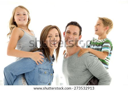 Happy young family having fun. Parents giving piggyback ride to their kids. Horizontal shot over white background. - stock photo