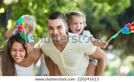 Happy young family holding kids with toy windmills at summer day  - stock photo