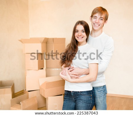 happy young family hugging on a background of cardboard boxes - stock photo