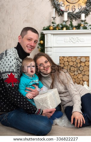 Happy young family in Christmas is smiling with presents. - stock photo