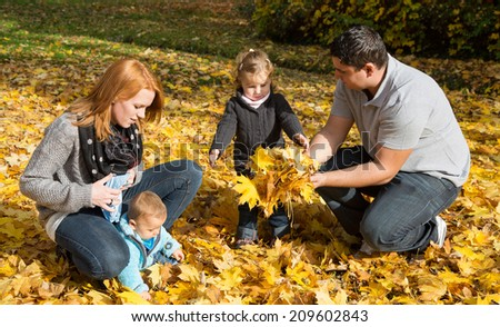 Happy young family in fall making a walk and play with maple leaves. - stock photo