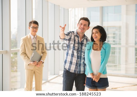 Happy young family looking round their new apartment - stock photo