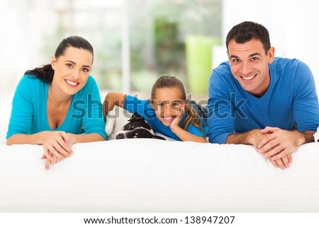 happy young family lying on bed with their pet dog at home - stock photo