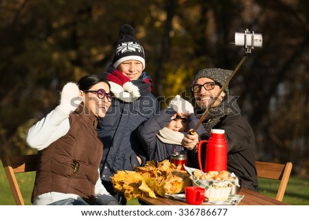 Happy young family making selfies while sitting at the wooden table. Parents and children posing and smiling for the camera. - stock photo